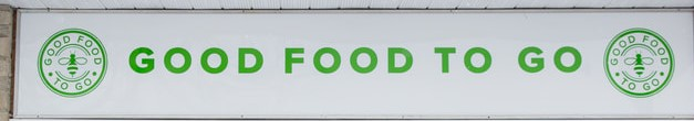 Green bees in a circle at each end of a banner, stating Good Food to Go.
